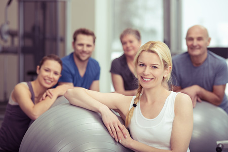 pilates: Attractive fit young woman in a pilates class at the gym posing leaning on her gym ball surrounded by a diverse group of people Stock Photo