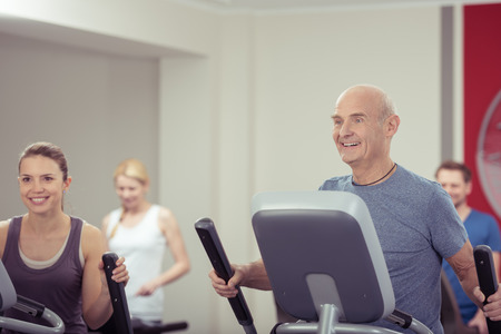 Group of diverse people working out together at the gym with focus to a smiling young woman and fit senior man in the foreground in a health and fitness concept Stock Photo
