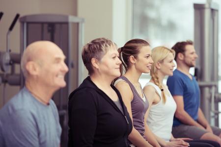 terapia de grupo: Fila de diversas personas jóvenes y mayores en un gimnasio sentado escuchando al instructor, con especial atención a una señora mayor en el centro en un concepto de estilo de vida saludable Foto de archivo