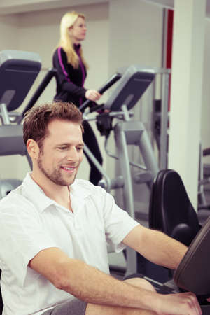 readout: Handsome young man watching the electronic readout as he exercises at the gym in a health and fitness concept