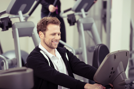 keeping room: Enthusiastic young man working out in a gym smiling happily as he watches the digital readout on the monitor showing his performance