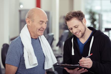 datos personales: Entrenador sonriente que trabaja con un hombre mayor en las notas de la escritura gimnasio en un portapapeles con una sonrisa de aliento en un concepto de salud y fitness