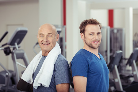 Two fit healthy men posing back to back at the gym, one senior and one young, looking at the camera with smiles full of vitality in a health and fitness concept