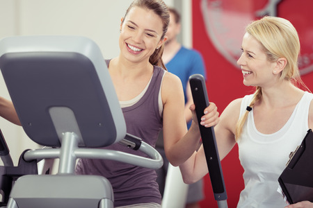 readout: Two young woman enjoying their exercise routine at the gym laughing and smiling as they watch the digital readout on the machine in a healthy lifestyle concept Stock Photo