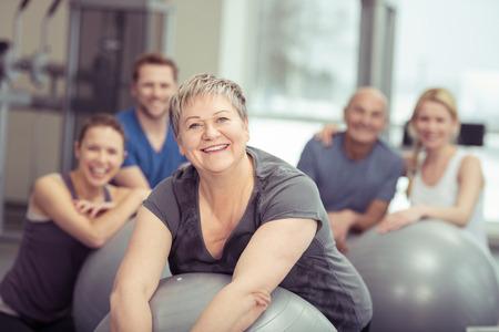 Glimlachend senior vrouw genieten van pilates klasse in de sportschool poseren leunend op haar bal lachend naar de camera met de klas achter