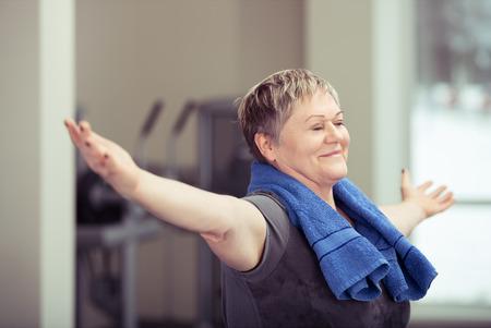 Happy starszy kobieta robi ćwiczenia aerobiku na siłowni stojących z wyciągniętymi rękami i uśmiech zadowolenia na twarzy