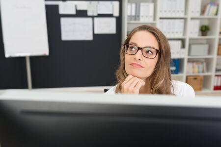 carreer: Thoughtful Pretty Young Office Girl with Blond Hair Wearing Eyeglasses, Looking Up with Hand on the Chin.