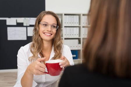 amigas conversando: Sonriente mujer bastante joven Oficina Hablar con ella Mujer Oficina compañero mientras que haciendo una taza de café durante Break Time. Foto de archivo