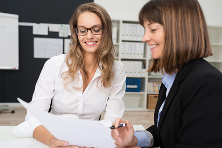 client meeting: Close up Two Happy Young Businesswomen at the Office Talking About Business Report on Paper. Stock Photo