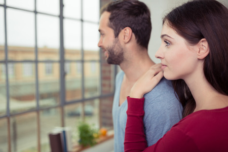 two visions: Young couple standing close together watching something in the street below out of a window in their apartment Stock Photo