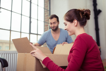 houses house: Attractive young couple moving house getting ready to unpack a cardboard carton of personal possessions below a big window Stock Photo