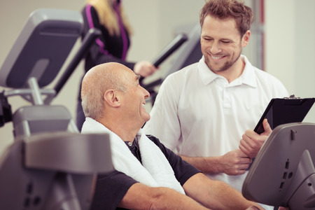 Attractive male trainer in a gym working with a senior man on equipment in a healthy active lifestyle concept Stock Photo