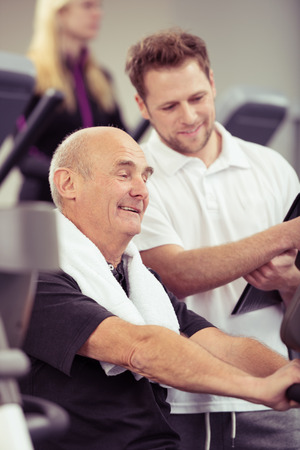 aide � la personne: Senior homme travaillant avec un entra�neur dans un gymnase comme ils lisent le moniteur sur l'�quipement ensemble pour voir comment il a jou� dans une salle de fitness et le concept de mode de vie sain Banque d'images