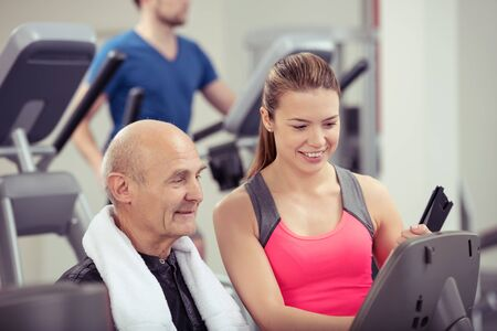 readout: Young woman monitoring a senior man in a gym discussing his performance with him as they check the readout on the equipment Stock Photo