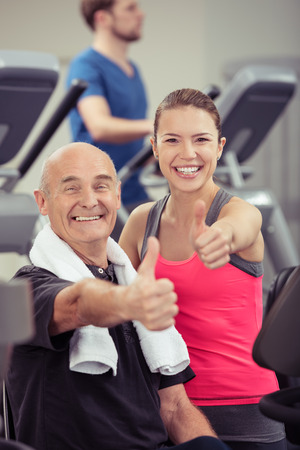alright: Smiling older man and young woman in a gym standing together amongst the equipment during a workout giving an enthusiastic thumbs up gesture of approval