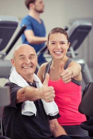 aide à la personne: Sourire homme plus âgé et jeune femme dans un gymnase debout ensemble parmi les équipements au cours d'une séance d'entraînement donnant une pouces enthousiastes geste d'approbation