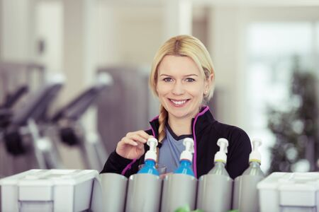 quench: Smiling pretty young woman taking a high energy drink from a dispenser at the gym to quench her thirst after a workout