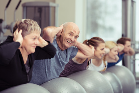 exercises: Elderly couple doing pilates class at the gym with a group of diverse younger people balancing on the gym ball with raised arms to tone their muscles in an active retirement concept