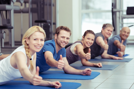 unanimous: Aerobics class at the gym giving a unanimous thumbs up of approval as they lie smiling on their exercise mats Stock Photo