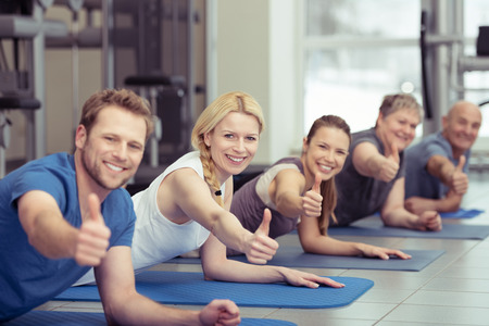 Diverse group of happy healthy people exercising at a gym on their exercise mats all looking at the camera giving a thumbs up of approval Stockfoto