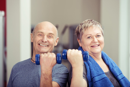 flexed: Fit elderly couple working out with weights each holding a dumbbell in a flexed hand as they tone their muscles and looking at the camera with happy smiles Stock Photo