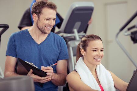 readout: Young woman smiling in satisfaction at the gym as she and her trainer look at the readout on the equipment monitor