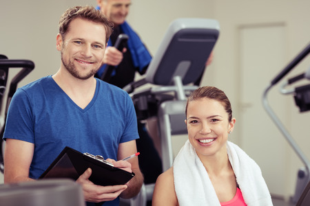 ion: Handsome young trainer with a pretty girl at the gym working out together ion the equipment as he monitors her progress