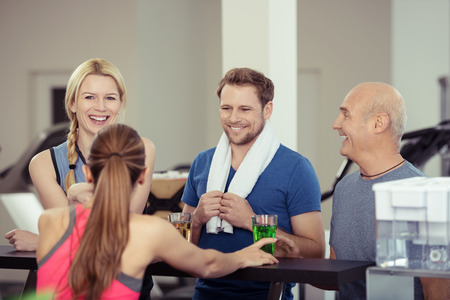 refreshments: Happy group of diverse friends enjoying refreshments at the gym after a workout chatting and laughing