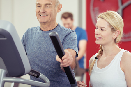 readout: Elderly man working out at a gym monitoring his progress with an attractive young female trainer on the readout on the equipment