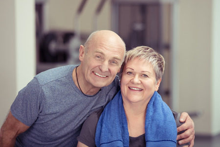 senior fitness: Fit affectionate elderly couple standing arm in arm at the gym looking at the camera with happy healthy smiles conceptual of an active retirement