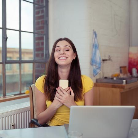 Romantique jeune femme souriante dans le bonheur comme elle étreint son téléphone portable sur sa poitrine après avoir reçu un message d'appel ou le texte alors qu'elle est assise à la maison de travail sur un ordinateur portable Banque d'images - 36448032