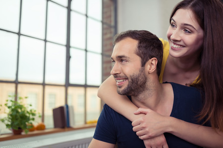 they are watching: Happy bearded young man and woman watching through a window with beaming smiles as they stand in a loving embrace inside their apartment Stock Photo