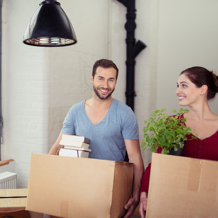 moving house: Happy Young Couple Carrying Cardboard Boxes Moving Into New Home.