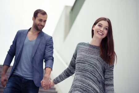 leading the way: Happy couple walking hand in hand in an urban environment with the young woman leading the way with a friendly smile Stock Photo