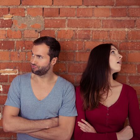 disgruntled: Disgruntled couple ignoring one another after an argument standing looking in opposite directions with folded arms Stock Photo