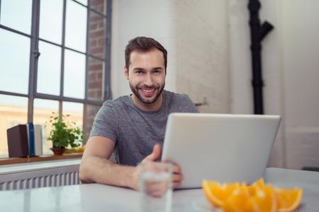 working at home: Apuesto joven con una sonrisa encantadora que se sienta en una mesa en su casa trabajando en su computadora port�til