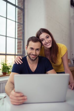 arms around: Loving couple posing for a portrait with their arms around each other as they sit behind a laptop computer in the apartment looking at the camera with a smile Stock Photo