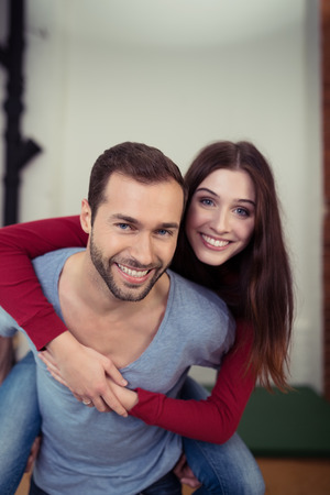 piggy back: Playful young couple romping at home with the young man giving his wife a piggy back ride as they laugh at the camera Stock Photo