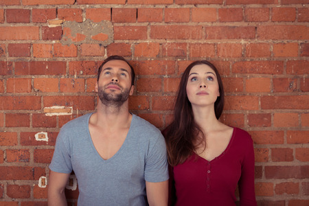 two visions: Couple standing thinking together leaning side by side against a brick wall looking into the air as they try to solve a problem Stock Photo