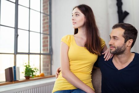 hands out: Young couple sitting close together relaxing at home watching out of a large window with serious expressions Stock Photo