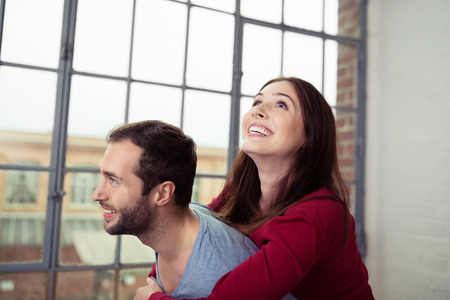 fro: Affectionate young couple relaxing at home with the pretty wife hugging her husband fro behind as she looks up into the air with a smile Stock Photo