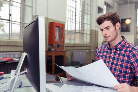 revisando documentos: Cierre de Handsome Oficina Hombre Revisar los documentos mientras que se sienta en su escritorio