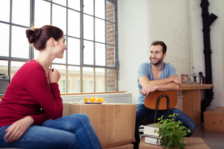couple talking: Happy Young Couple Talking at the Living Room of their New Home. Stock Photo