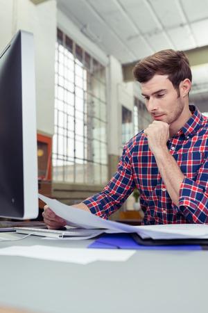 revisando documentos: Cerrar un joven serio trabajador var�n repasan documentos en su mesa de trabajo.