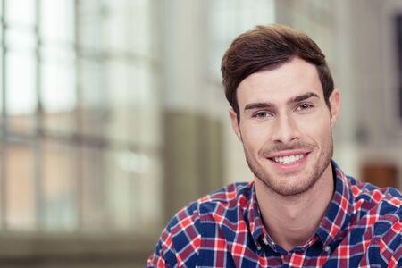 volto uomo: Primo piano Bello uomo in camicia a scacchi, sorride alla macchina fotografica. Sottolineando Copy Space.