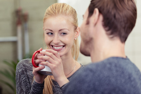 chats: Smiling pretty woman drinking coffee as she chats with her husband smiling happily at him over the rim of the mug