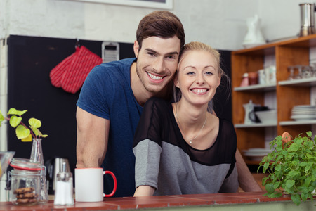happy couple: Happy young couple in their kitchen posing with their heads close together behind the counter smiling at the camera Stock Photo