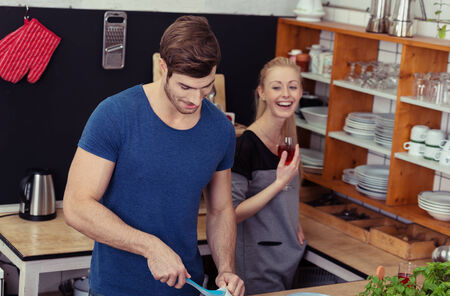attempts: Pretty young woman standing laughing at her husband in the kitchen as he attempts to prepare the meal Stock Photo