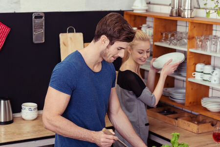kitchenette: Young couple cooking dinner in a kitchenette with the wife getting plates off the shelf while watching her husband preparing to serve the food Stock Photo