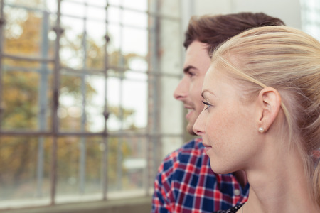 profil: Profile view of an attractive young couple standing looking out of the window into a tree lined urban street watching something outdoors, close up headshots